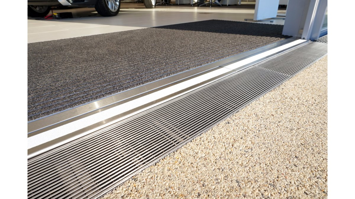 Level entry strip drain in car showroom doorway by Allproof.